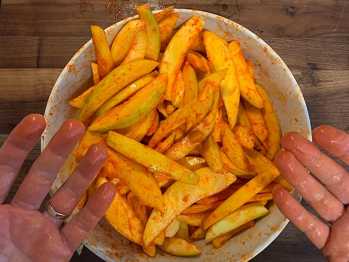 adding li hing to sliced mangoes for pickled mango recipe