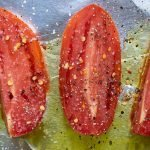 adding seasoning for oven roasted tomatoes